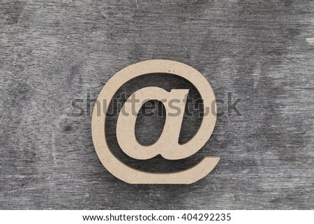 email symbol on grunge wood background (Commercial At Symbol)  - stock photo