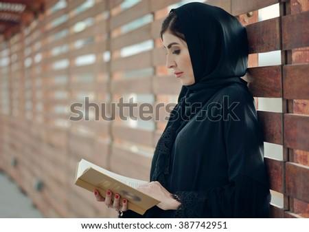 Emarati Arab woman outside reading a book, Dubai, United Arab Emirates. - stock photo