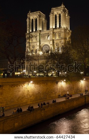 Embankment of Seine River and Notre Dame de Paris at night - stock photo