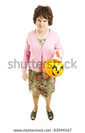 Embarassed father dressed up as a woman on Halloween, carrying a pumpkin bucket of candy.  Full body isolated on white. - stock photo