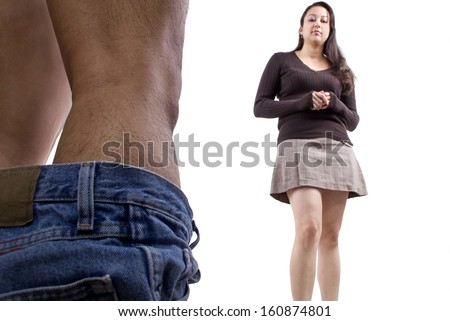 embarassed man with pants down while woman makes fun of his manhood - stock photo