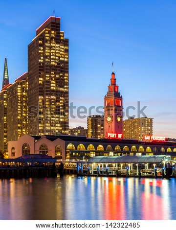 Embarcadero Towers and Ferry Building in San Francisco, illuminated in red and gold colors. - stock photo
