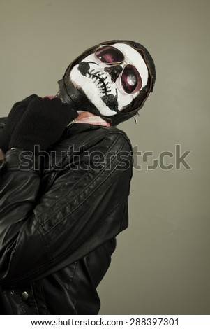 Embarrassed aviator with face painted as human skull - stock photo