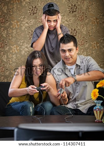 Embarrassed Hispanic teenager behind parents playing video games - stock photo