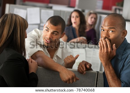 Embarrassed man with hand over mouth standing with coworkers - stock photo