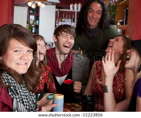 Embarrassed woman at a table with laughing friends - stock photo