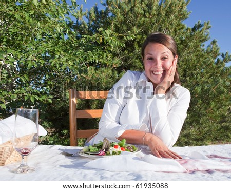 Embarrassed woman trying to cover wine that she spilled on white table cloth - stock photo