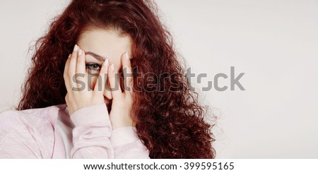 embarrassed young woman covering face with hands and peeking through her fingers - stock photo