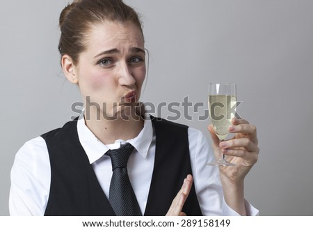 Embarrassed young woman wearing uniform of wine waitress refusing glass of white bubbly wine - stock photo