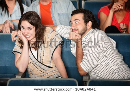 Embarrassed young woman with flirting boyfriend in theater - stock photo