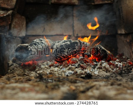 Embers and fire above firebrand in hearth, shallow DOF - stock photo
