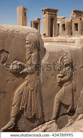 Embossed bas relief carvings of servants bringing gifts to the Achaemenian King on the sidewall of stairs in front of Tachara Palace or Palace of Darius in Persepolis of Shiraz. - stock photo
