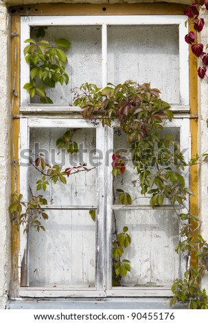 Embowered old window in abandoned house - stock photo