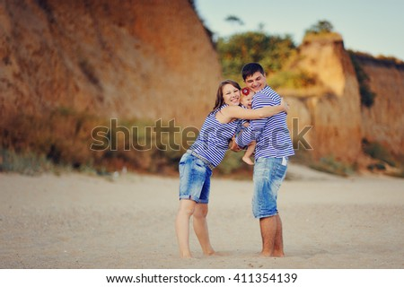 embrace each other on vacation in the summer a cheerful young family with the daughter