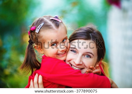 Embrace mother with  little daughter. Mom and child girl. Happy family. Shallow depth of field. Selective focus. - stock photo