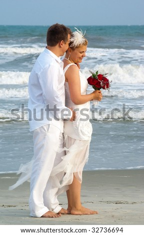 Embrace of bride and groom at the oceanfront - stock photo