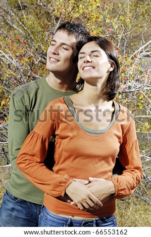 embraced couple standing in the sun - stock photo