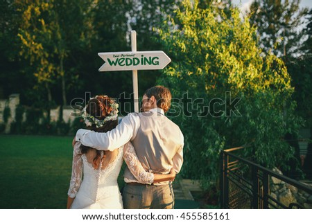 Embracement of the newlyweds next to the wedding sign - stock photo
