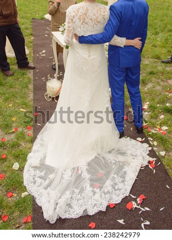 embracing bride and groom at ceremony in park - stock photo