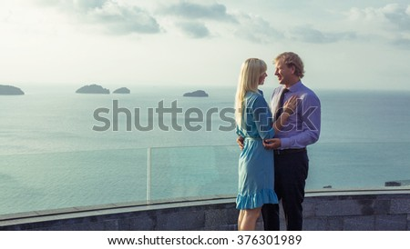 Embracing couple of blond man and blond woman in formal wear in the sea view point. Tropical islands on the background. - stock photo
