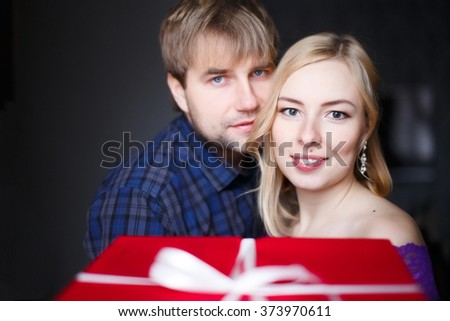 embracing couple receives a gift from someone. hugging couple in love get gift from somebody. beautiful girl and the guy get a gift box. looking at the camera. selective focus - stock photo