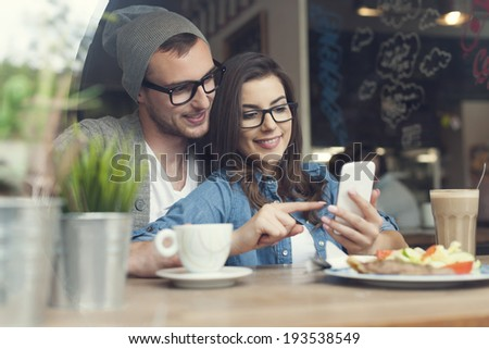 Embracing couple using mobile phone in cafe  - stock photo
