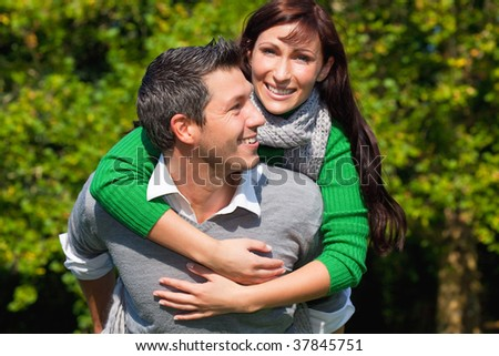 Embracing lovely lovers having fun in cold season outdoors enjoying the togetherness - stock photo