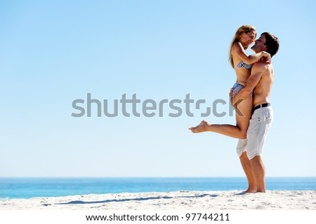 embracing summer beach couple hugging and laughing together on a tropical island - stock photo