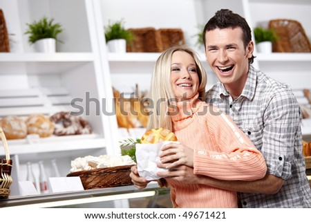 Embracing young couple in a baker's shop - stock photo