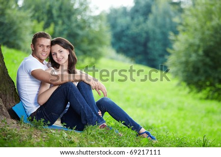 Embracing young couple in the park - stock photo