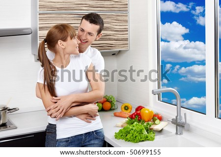 Embracing young enamoured couple at kitchen - stock photo