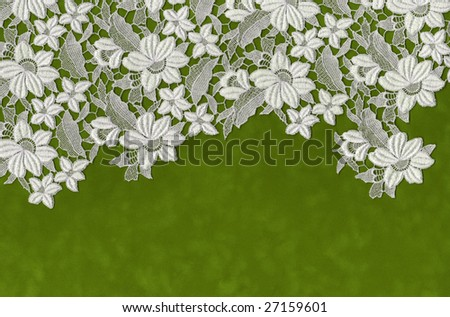 embroidered flowers laid over green velvet paper - stock photo