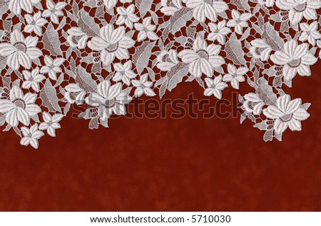 embroidered flowers laid over red velvet paper - stock photo