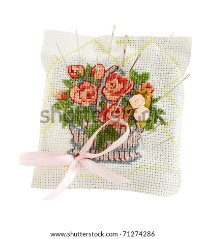Embroidered pillow with the needles on the white - stock photo