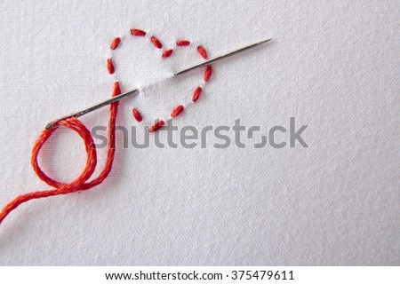 Embroidered red heart on a white cloth close up.  Concept passion for sewing and embroidery. Horizontal composition.Top view - stock photo