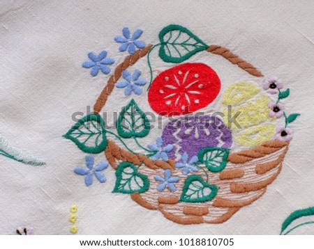 Embroidered white linen tablecloth. Basket with Easter eggs, leaves and flowers on white background.  Close up, selective focus.
