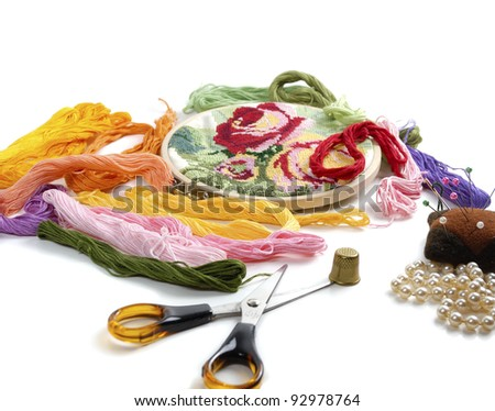 embroidery and colorful threads on white background - stock photo