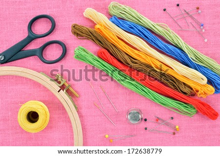 Embroidery and cross stitch accessories on pink linen fabric. Embroidery hoop, scissors, thread, needles, thimble. Copy space. - stock photo