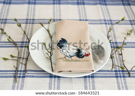 embroidery on a plate with chicken, a feather and branches