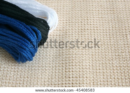 Embroidery threads on a beige canvas, a horizontal picture - stock photo