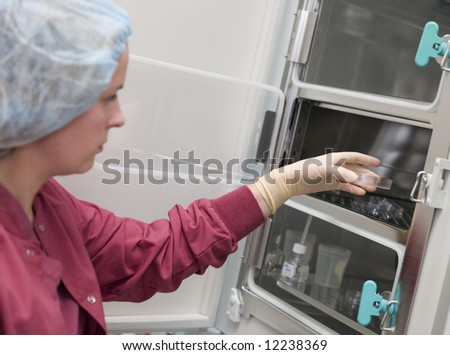 Embryologist putting sample into incubator in laboratory - stock photo