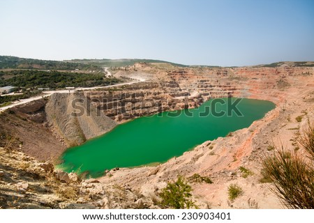 Emerald green lake in flooded opencast mine, open pit. Oval lake in mining industrial crater, acid mine drainage in rock. Open pit mine with lake. Quarry fluxes for the industry. - stock photo