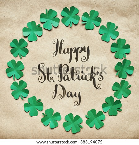 Emerald green paper clover shamrock leafs wreath border frame on craft paper eco background. St. Happy St. Patrick's Day brush nib lettering calligraphy square postcard. - stock photo