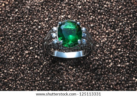 Emerald ring with diamonds on sand background - stock photo