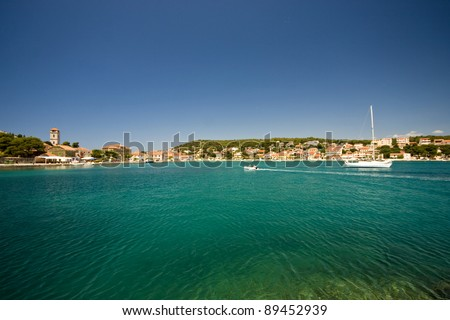 Emerald sea water and the lovely houses in Tisno - stock photo