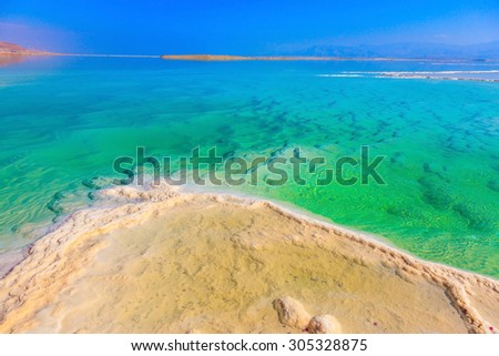 Emerald water of the Dead Sea. Fused salt made on the surface of the water - stock photo