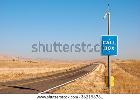 Emergency call box sits off to the side on a rural highway. - stock photo