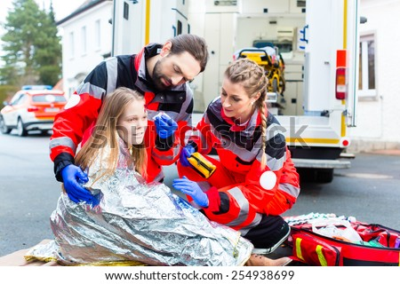 Emergency doctor and paramedic or ambulance team helping accident victim  - stock photo