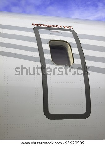 Emergency Escape An emergency escape door of a passenger jet airplane. Vertical. - stock photo