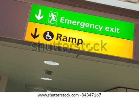 emergency exit and handicapped ramp sign at a international airport corridor - stock photo